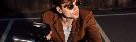 Photo for Panoramic shot of handsome man in sunglasses sitting on motorcycle and looking away - Royalty Free Image