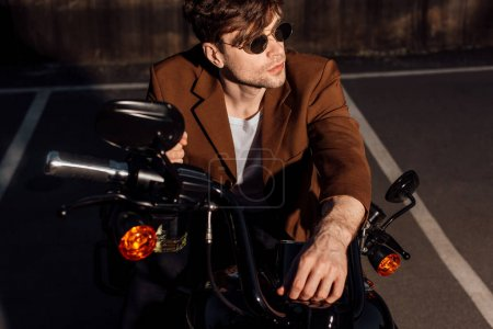 Photo for Handsome man in sunglasses sitting on motorcycle and looking away - Royalty Free Image