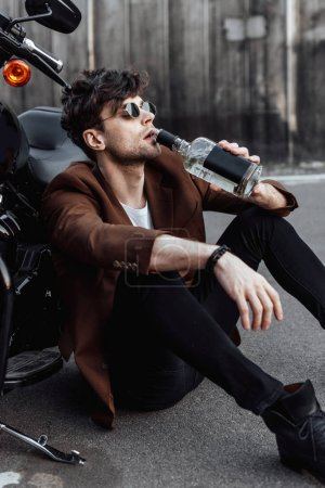 Photo for Young man drinking alcohol while sitting on ground near motorcycle - Royalty Free Image