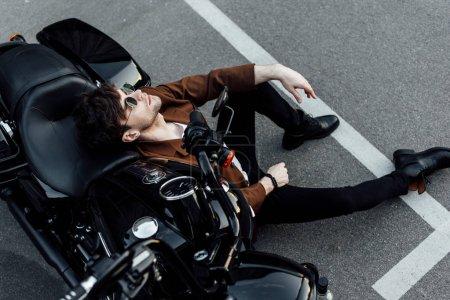 Photo pour Vue supérieure de l'homme se reposant tout en se penchant sur la moto de balck et s'asseyant sur l'alphalt - image libre de droit