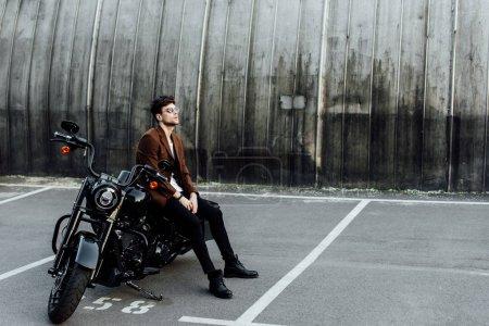 Photo pour Vue pleine longueur de bel homme dans la veste se reposant sur la moto noire et regardant loin - image libre de droit