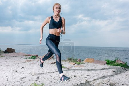 Photo for Sportive blonde woman running and listening music in earphones near sea - Royalty Free Image