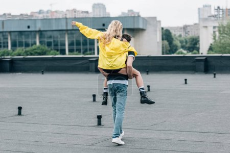 Photo for Back view of woman in yellow jacket playing with man on roof - Royalty Free Image
