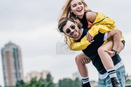 Photo pour Femme attirante et bel homme souriant et jouant sur le toit - image libre de droit