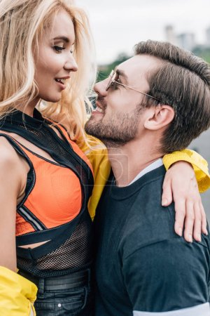 Photo for Handsome man in glasses holding attractive woman on roof - Royalty Free Image