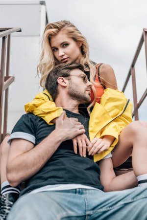 Photo for Blonde woman and handsome man in glasses hugging on roof - Royalty Free Image