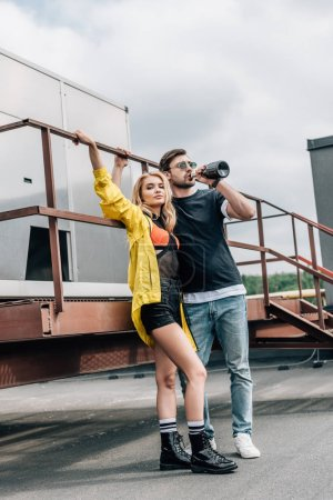 Photo for Blonde woman and handsome man drinking champagne on roof - Royalty Free Image