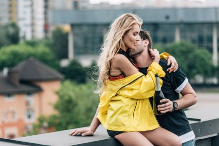 Photo pour Bouteille de fixation d'homme, embrassant et étreignant la femme attirante - image libre de droit