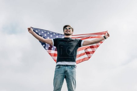 Photo for Handsome man in glasses holding american flag and smiling on roof - Royalty Free Image
