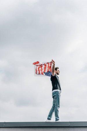 Photo pour Vue de côté de l'homme beau dans des jeans et le t-shirt retenant le drapeau américain - image libre de droit