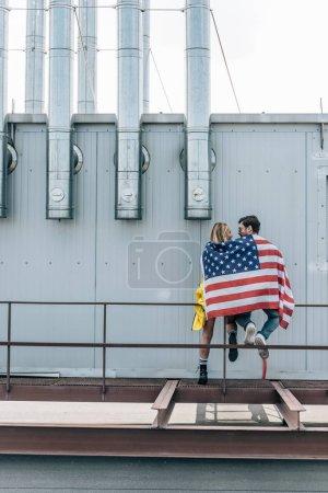 Photo pour Vue arrière de la femme et de l'homme avec le drapeau américain sur le toit - image libre de droit