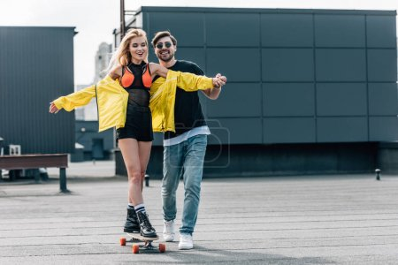 Photo for Attractive and smiling woman skateboarding and man in glasses hugging her - Royalty Free Image