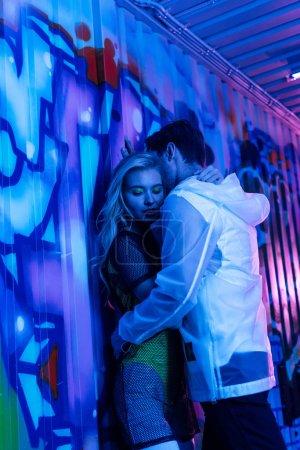 Photo pour Attrayant et blonde femme étreignant avec l'homme près du mur - image libre de droit