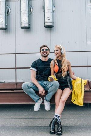Photo pour Femme attrayante et blonde avec écouteurs utilisant un smartphone et souriant avec l'homme - image libre de droit