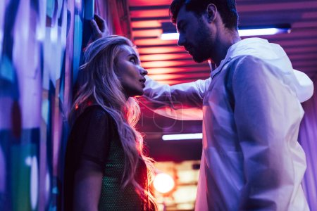 Photo pour Vue de côté de la femme attirante et blonde parlant avec l'homme - image libre de droit