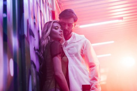 Photo for Attractive and blonde woman hugging with handsome man in night club - Royalty Free Image