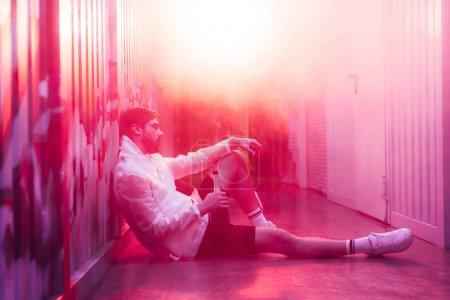 Photo pour Vue de côté de l'homme beau s'asseyant sur l'étage et retenant la bouteille - image libre de droit