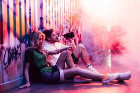 Photo pour Femme attirante et blonde s'asseyant sur l'étage et le champagne bel homme buvant - image libre de droit