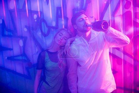 Photo pour Belle et blonde femme aux yeux fermés et bel homme buvant du champagne - image libre de droit