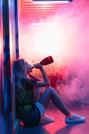 Photo pour Vue de côté de la femme attirante et blonde s'asseyant sur l'étage et buvant le champagne - image libre de droit