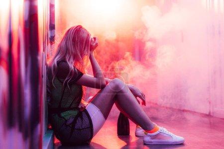 Photo pour Vue latérale de la femme blonde et triste assise sur le sol - image libre de droit