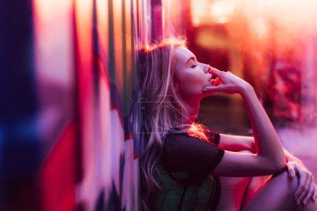 Photo pour Vue latérale de la femme blonde avec les yeux fermés assis près du mur - image libre de droit
