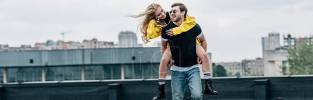 panoramic shot of attractive and blonde woman and handsome man hugging and playing on roof