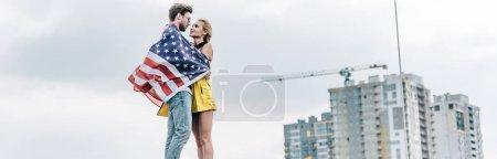 Photo pour Tir panoramique de l'homme avec le drapeau américain étreignant avec la femme attirante et blonde - image libre de droit