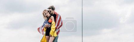 Foto de Foto panorámica del hombre con la bandera americana abrazando con mujer atractiva y rubia - Imagen libre de derechos