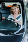 """Постер, картина, фотообои """"selective focus of cheerful woman holding steering wheel while driving car """""""