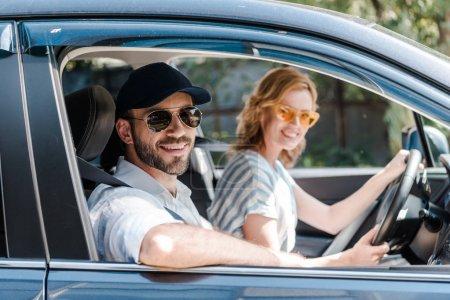 Photo pour Foyer sélectif de l'homme heureux dans des lunettes de soleil souriant près de la voiture de conduite attirante de femme - image libre de droit