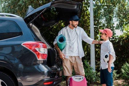Photo pour Père retenant le tapis de forme physique et regardant le fils avec le football près de la voiture - image libre de droit