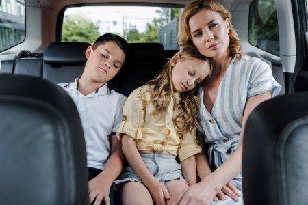 Photo pour Foyer sélectif des enfants de sommeil près de la mère attirante dans la voiture - image libre de droit