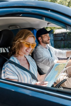 Photo for Selective focus of cheerful woman holding map while man driving car - Royalty Free Image