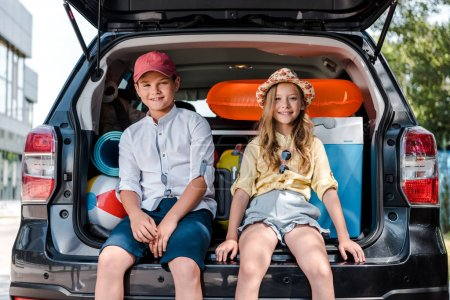 Photo for Happy sister and brother sitting on car trunk and looking at camera - Royalty Free Image