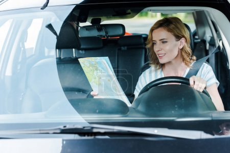 Photo for Selective focus of woman looking at map and driving car - Royalty Free Image