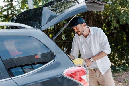 Photo pour Homme heureux en chapeau mettre sac de voyage dans le coffre de la voiture - image libre de droit