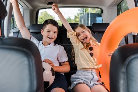 Photo for Selective focus of cheerful sister and brother celebrating and gesturing in car - Royalty Free Image