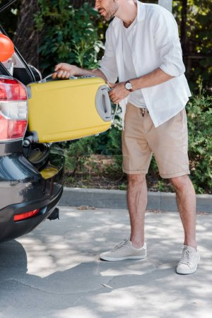 Photo for Cropped view of happy man in cap putting travel bag in car trunk - Royalty Free Image