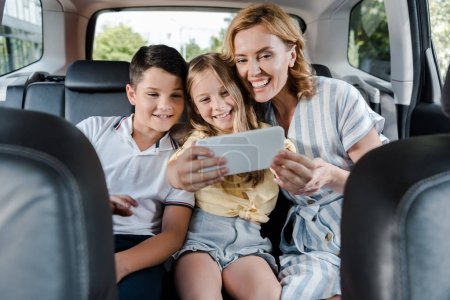 Photo pour Selective focus of cheerful family taking selfie on smartphone in car - image libre de droit