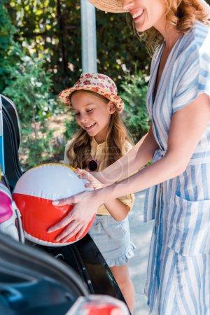 Photo pour Vue recadrée de mère mettant la bille de plage dans la voiture près de la fille - image libre de droit