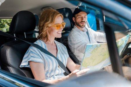 Photo pour Foyer sélectif de femme dans des lunettes de soleil regardant la carte dans la voiture près de l'homme - image libre de droit