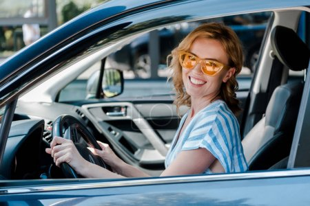 Photo for Happy blonde woman in sunglasses holding steering wheel while sitting in car - Royalty Free Image
