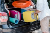 """Постер, картина, фотообои """"cropped view of man putting yellow luggage near pink suitcase in car trunk """""""