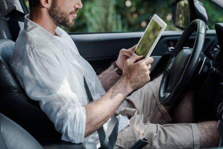 Photo pour Vue recadrée de l'homme barbu s'asseyant dans la voiture et utilisant la tablette numérique - image libre de droit