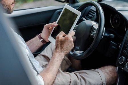 Photo pour Vue recadrée de l'homme assis dans la voiture et en utilisant une tablette numérique - image libre de droit