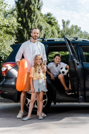 Photo pour Cheerful father and happy children standing near car - image libre de droit