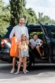 "Постер, картина, фотообои ""cheerful father and happy children standing near car """