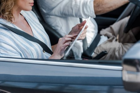 Photo for Cropped view of woman using digital tablet near driver in car - Royalty Free Image
