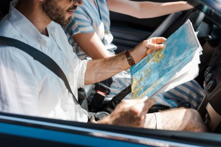 Photo for Cropped view of man holding map near woman in car - Royalty Free Image